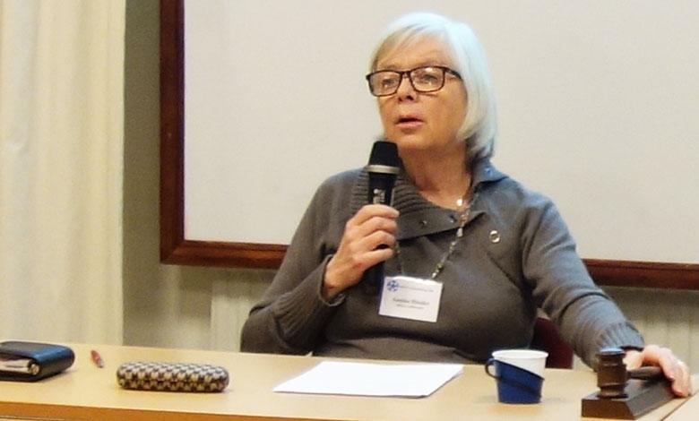 Annika Hässler med mikrofon i ena handen och ordförandeklubba i den andra
