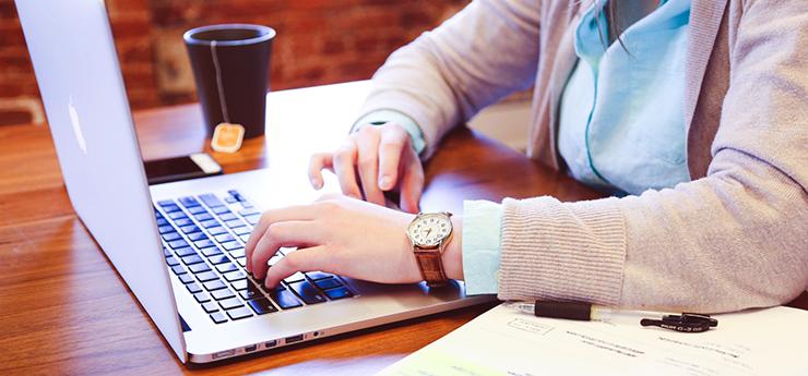 En person använder en laptop intill en full temugg