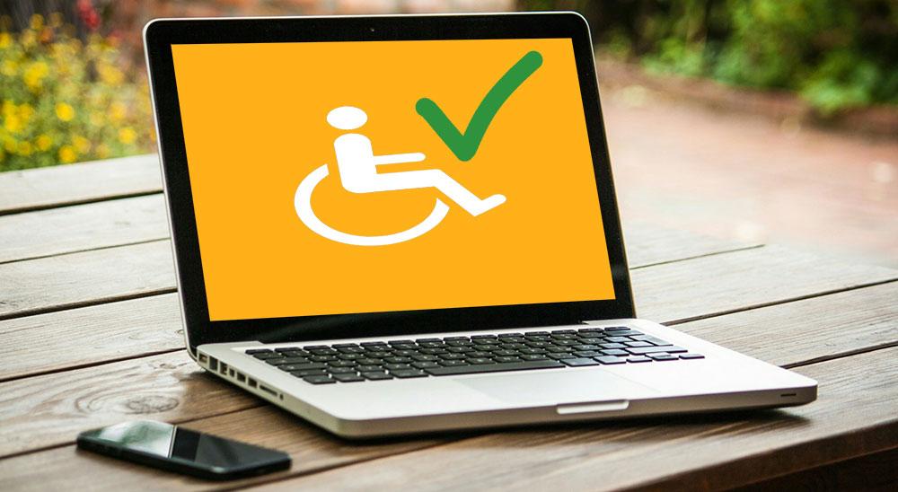 En laptop på ett träbord. På datorskärmen syns symbolen med en person i rullstol intill en grön avbockning.