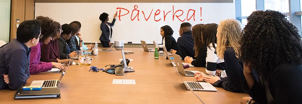 En grupp vid ett mötesbord ser mot en skrivtavla, med ordet Påverka!