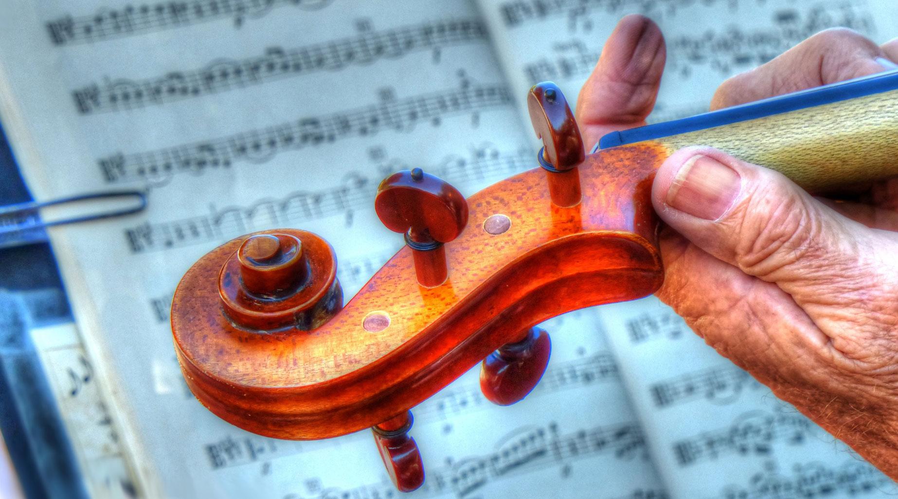 En rynkig hand håller i en fiol.