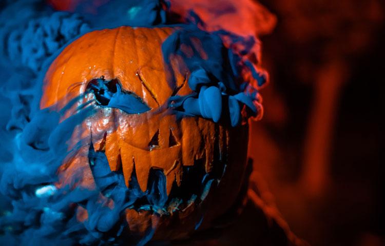 Ur en pumpas läskigt utkarvade ansikte väller blå rök ut.