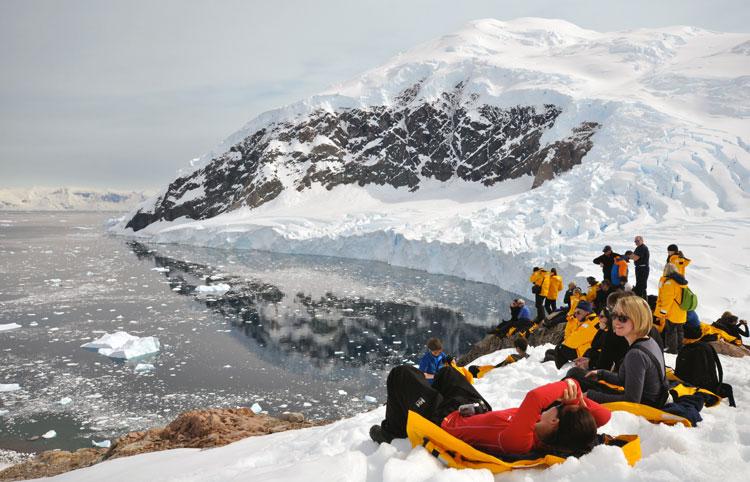 En grupp friluftsmänniskor njuter i snön intill en bergssjö