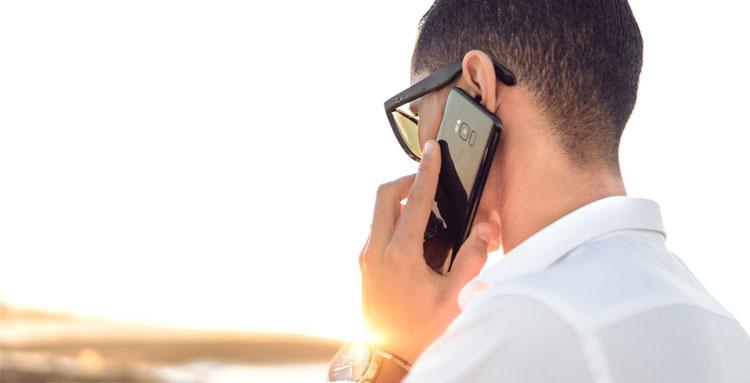 Person talar i telefon, framför en soluppgång