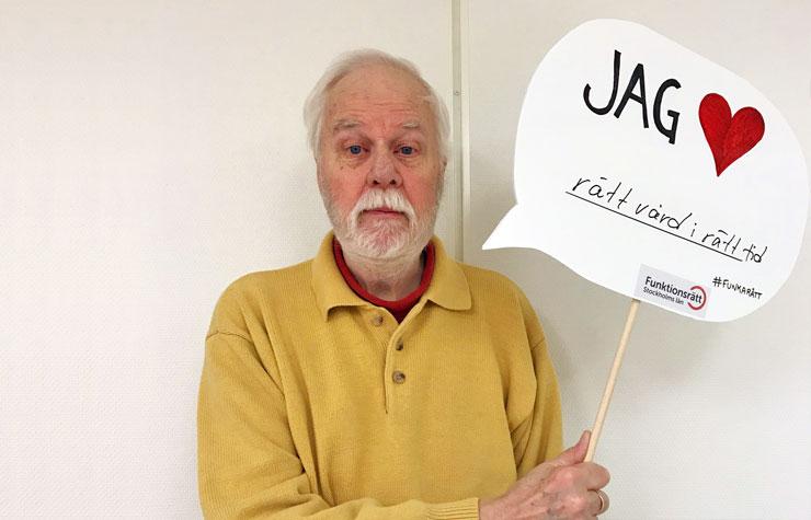 Lennart Håwestam håller upp en skylt med texten Jag hjärta rätt vård i rätt tid