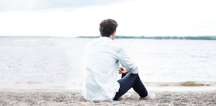En person sitter ensam på en strand, med ryggen mot kameran
