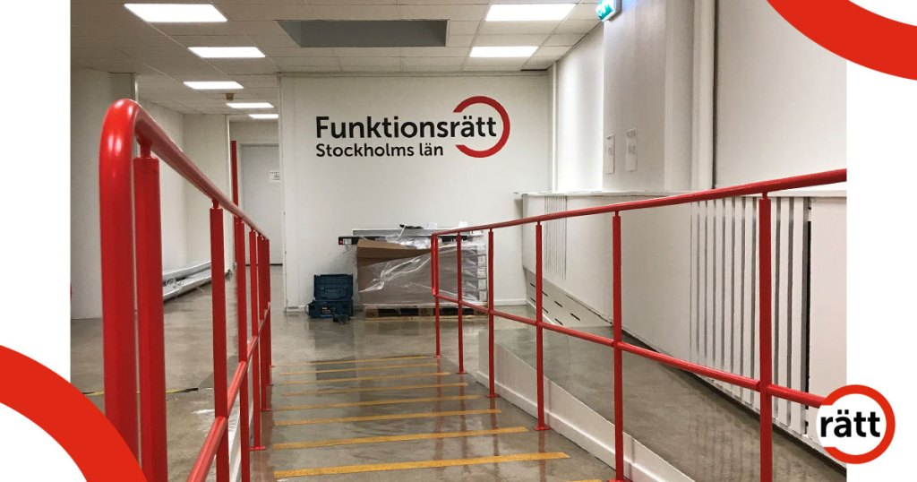 Ramp med rött räcke leder ner till lokalen med vita väggar och Funktionsrättsloggan
