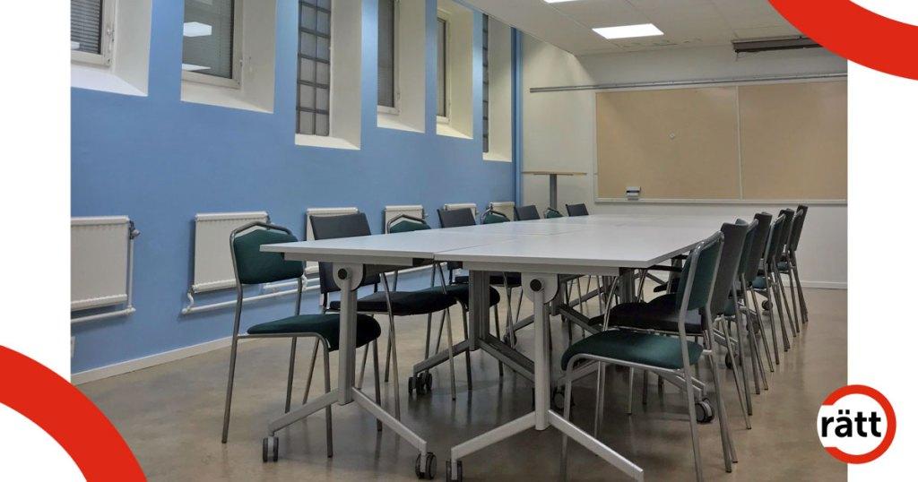 Flera lätta bord på hjul bildar ett stort konferensbord. Väggen i bakgrunden är målad ljusblå.