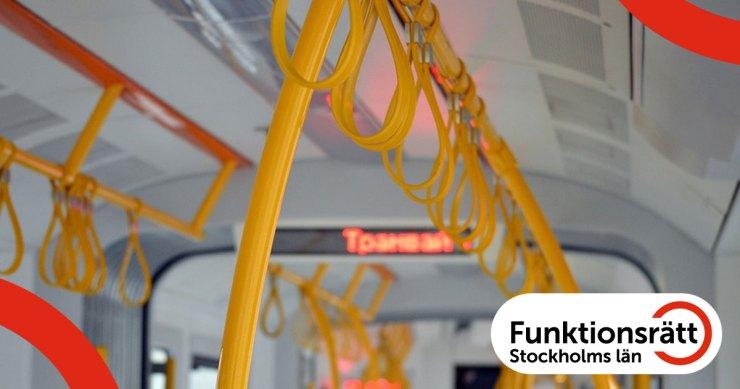Fotografi av inredningen från en spårvagn. Det finns gulmarkerade ledstänger och handtag samt en display som visar ett stationsnamn.