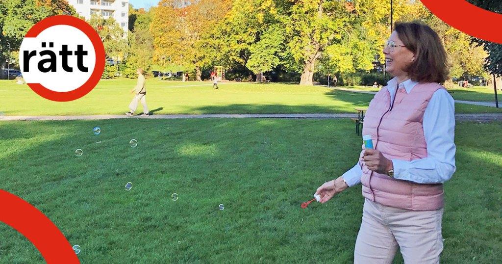 En glad kvinna blåser såpbubblor i parken.
