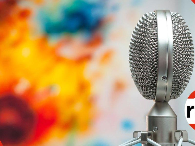 Mikrofon med en färgglad tavla i bakgrunden.